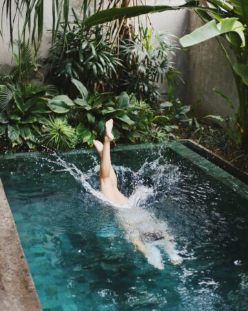 girl jumping into a pool during bali retreat
