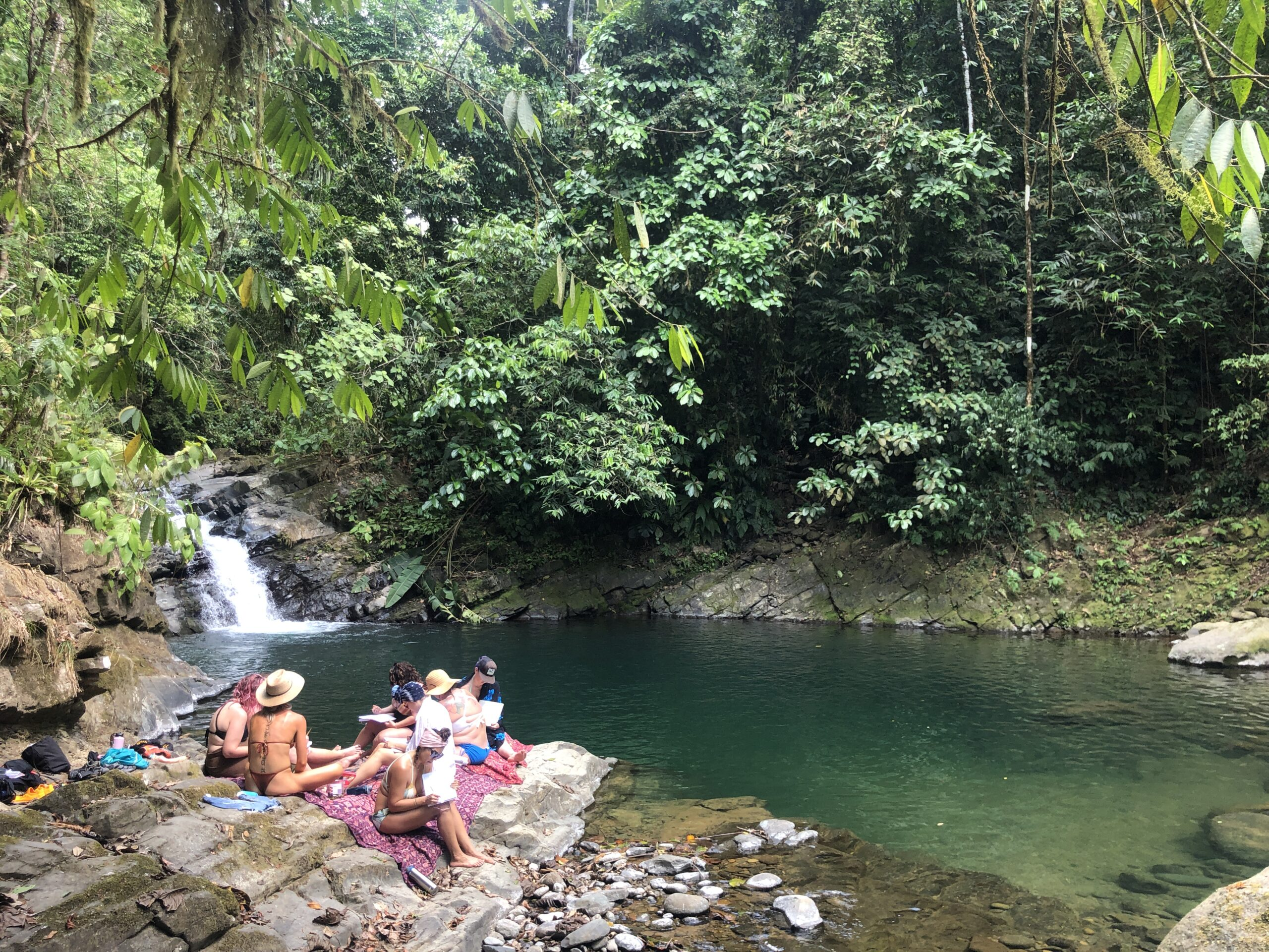 women hanging out by a waterfall during a costa rica retreat